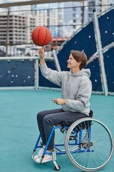 Женщина с инвалидностью сидит в инвалидной коляске и крутит мяч на пальце во время тренировки на открытом воздухе