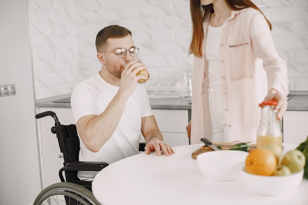Woman with disabled man in wheelchair having breakfast together at home.