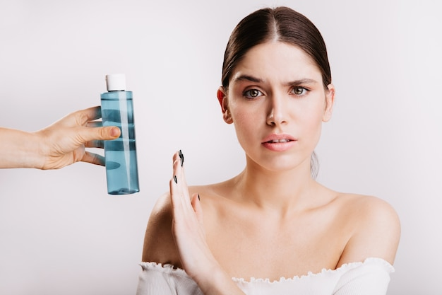 不快感のある女性は、青いボトルで強壮剤を使用することを拒否します。白い壁にきれいな肌を持つ不満の女の子のショット。