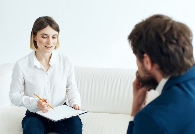서류를 가진 여자와 공석을 고용하는 소파에 앉아 양복을 입은 남자