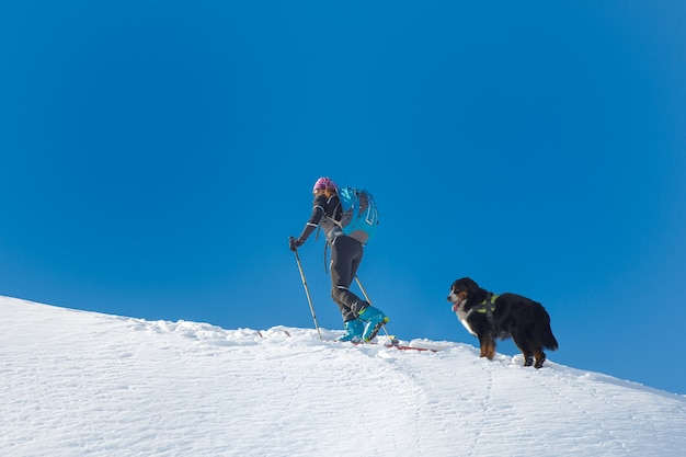 Woman with dog bernese in the mountains at sky