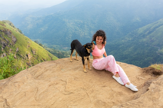 A woman with a dog enjoying the mountain scenery on the edge of a cliff