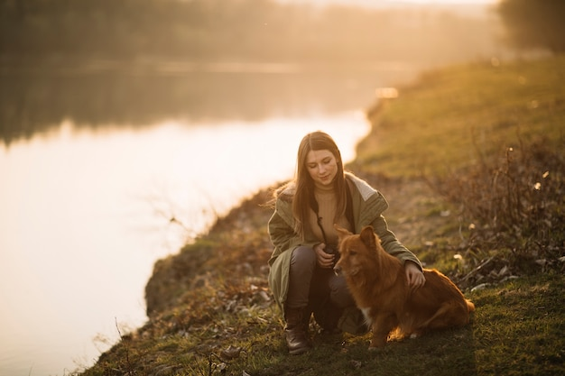 Женщина с собакой держит камеру