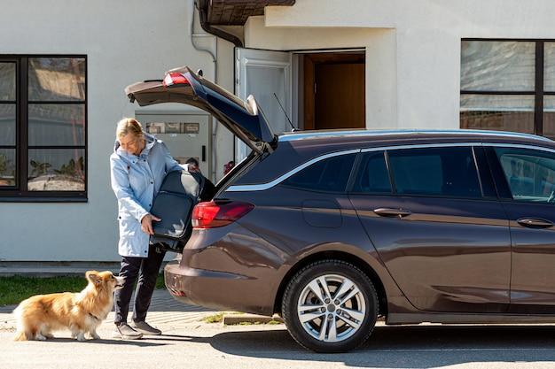 車のトランクにスーツケースを読み込んでいる犬を持つ女性