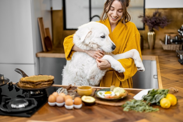 朝の台所で犬と女性