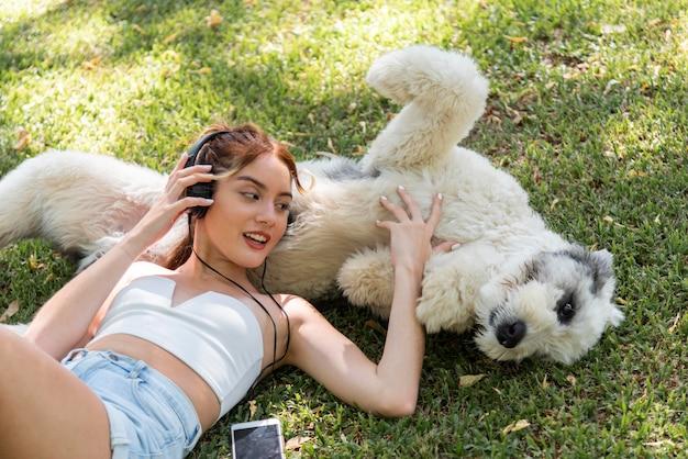 犬の屋外リスニング音楽を持つ女性