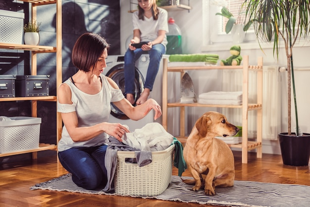 Woman with dog sorting clothes on the floor