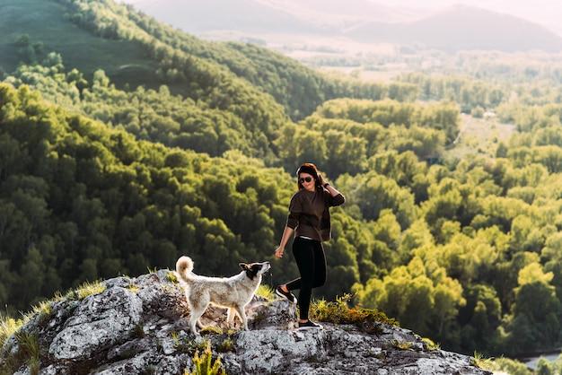 山を歩いている犬を持つ女性。犬の友達。ペットと歩いています。犬と一緒に旅行。ペット。スマート犬。