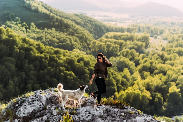 Woman with dog walking in the mountains. canine friend. walking with your pet. traveling with a dog. a pet. smart dog.