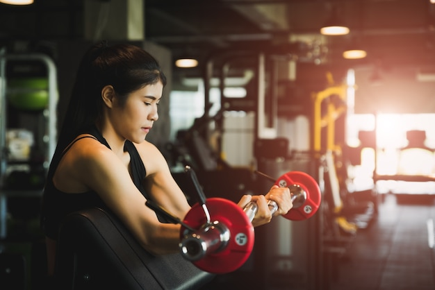 Woman with doing exercises with barbell. fitness, bodybuilding, healthy lifestyle concept.