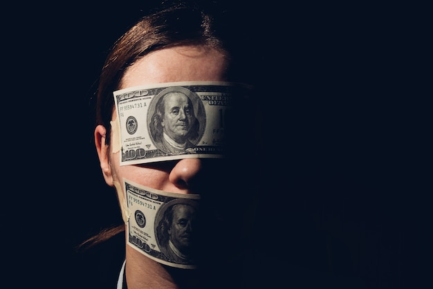 Woman with dollar bills covering her eyes