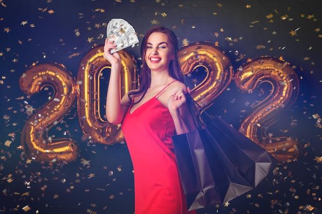 ドルと購入の女性は、ブラックフライデーの風船のクリスマスセールで新年の買い物をします