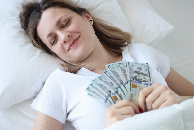Woman with dollars in hands sleeping in white bed. dreams of money concept
