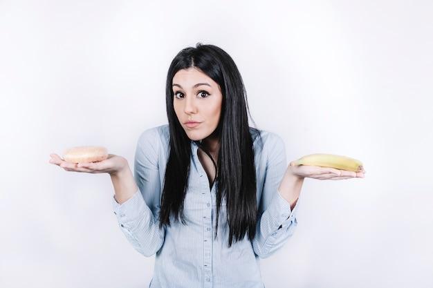 ドーナツとバナナを持つ女性