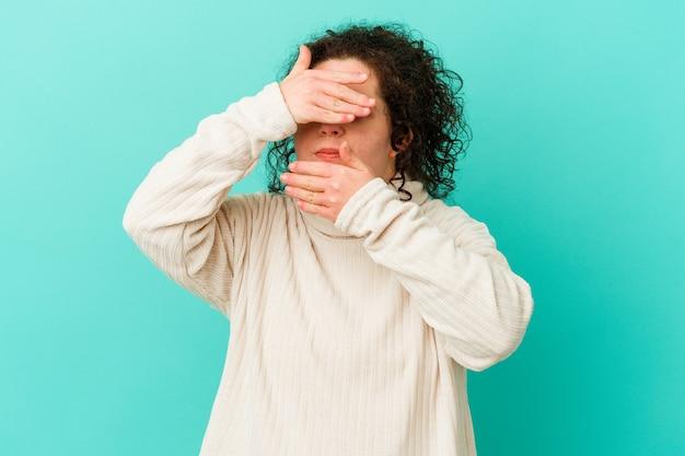 다운 증후군을 앓고있는 여성이 손가락으로 카메라를 깜빡 거리며 얼굴을 가리고 당황합니다.