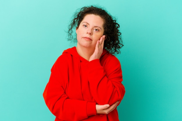 Woman with down syndrome isolated blows cheeks, has tired expression. facial expression concept.