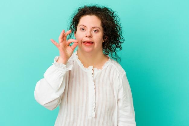 다운 증후군을 가진 여자는 쾌활하고 자신감이있는 확인 제스처를 보여주는 격리