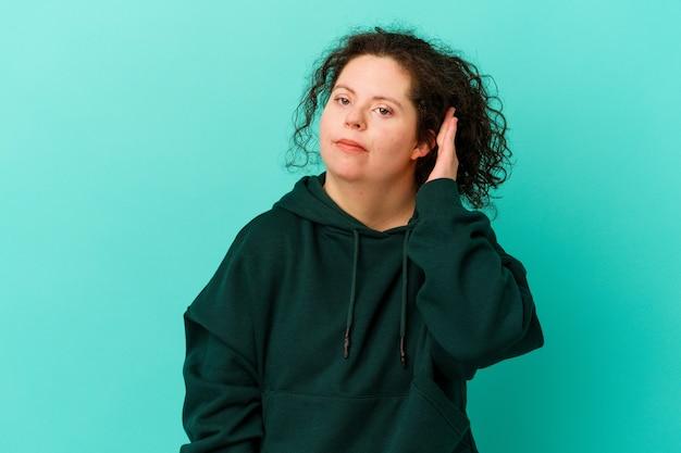 다운 증후군을 앓고있는 여성이 손가락으로 귀를 덮고 있으며, 큰 주변 환경에 스트레스를 받고 절망적입니다.