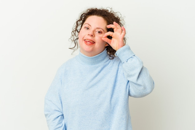 Woman with down syndrome isolated excited keeping ok gesture on eye.
