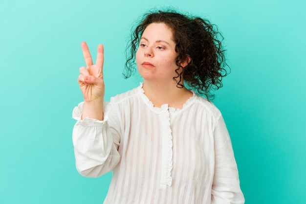 Woman with down syndrome isolated joyful and carefree showing a peace symbol with fingers.