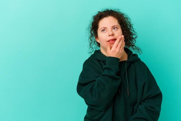 다운 증후군을 가진 여자는 행복하고 평온하고 자연스러운 감정을 웃고 있습니다.