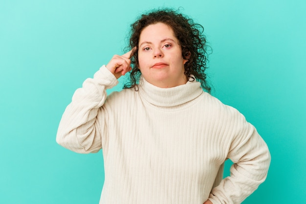 Woman with down syndrome isolated pointing temple with finger, thinking, focused on a task.