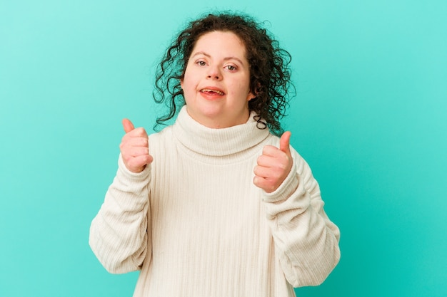 다운 증후군을 가진 여성은 두 엄지 손가락을 위로 올리고 웃고 자신감을 가지고 있습니다.