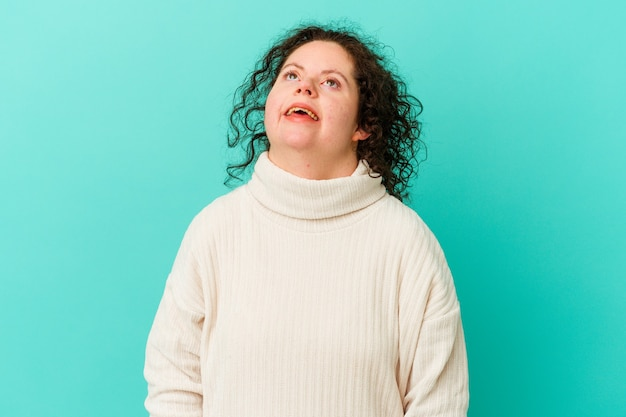 Woman with down syndrome isolated relaxed and happy laughing, neck stretched showing teeth.