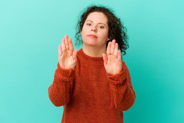 다운 증후군을 가진 여자는 정지 신호를 보여주는 뻗은 손으로 서서 당신을 방지합니다.