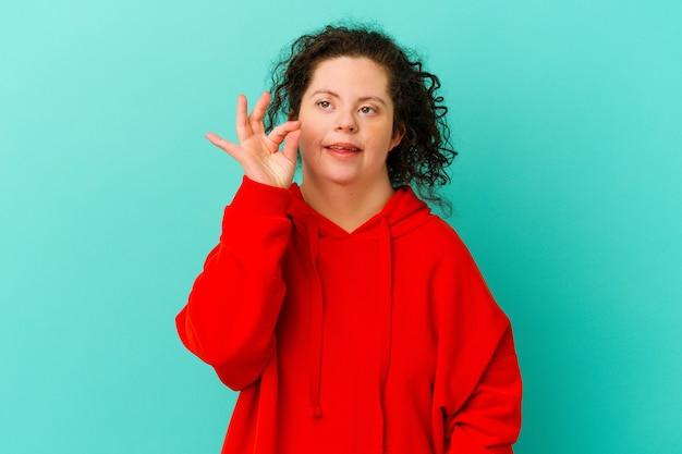 고립 된 다운 증후군을 가진 여성은 눈을 윙크하고 손으로 괜찮은 제스처를 유지합니다.