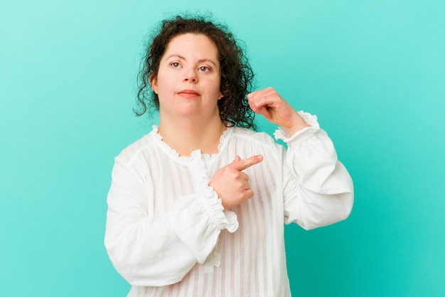 Женщина с синдромом дауна показывает жест силы руками, символ женской силы