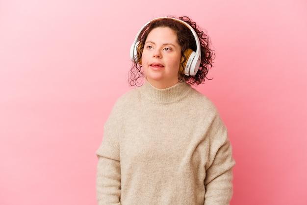ピンクの背景に分離されたヘッドフォンでダウン症の女性は混乱し、疑わしく、不安を感じます。