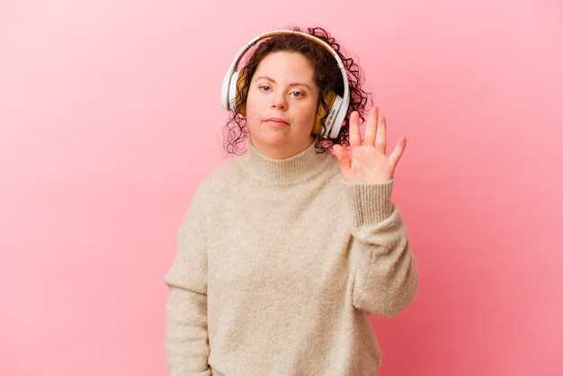 ピンクの背景に分離されたヘッドフォンでダウン症の女性は、指で5番目を示す陽気な笑顔をしています。