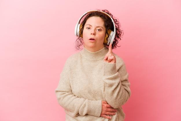몇 가지 좋은 생각을 갖는 분홍색 벽에 고립 된 헤드폰으로 다운 증후군을 가진 여자. 창의성의 개념