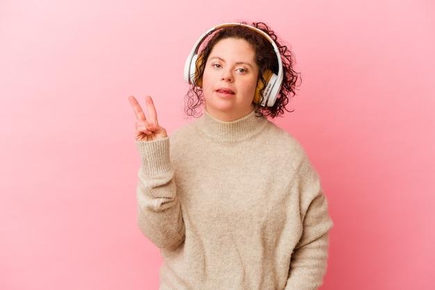 Женщина с синдромом дауна с наушниками, изолированными на розовой стене, радостной и беззаботной, показывая пальцами символ мира.