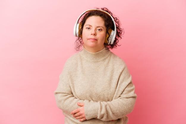 핑크 벽 웃음과 재미에 고립 된 헤드폰으로 다운 증후군을 가진 여자.