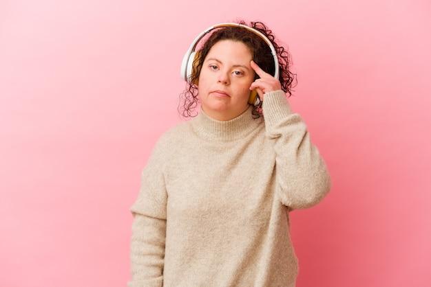 손가락으로 사원을 가리키는 분홍색 벽에 고립 된 헤드폰 다운 증후군을 가진 여자, 생각, 작업에 초점을 맞춘.