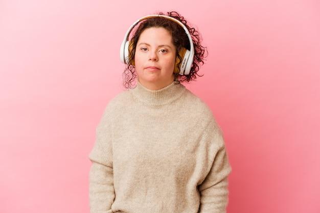 분홍색 벽에 고립 된 헤드폰으로 다운 증후군을 앓고있는 여성이 어깨를 으쓱하고 눈을 뜨고 혼란스러워합니다.