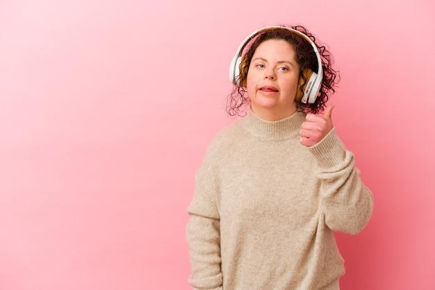 Женщина с синдромом дауна с наушниками, изолированными на розовой стене, улыбается и поднимает большой палец вверх