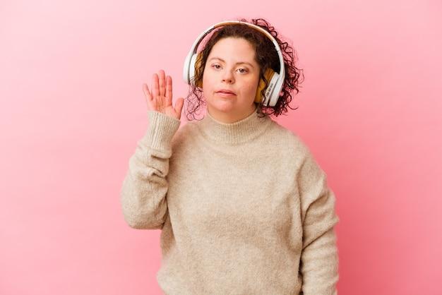 ゴシップを聴こうとしているピンクの壁に分離されたヘッドフォンでダウン症の女性