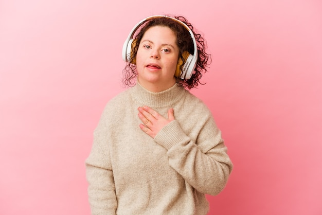 Woman with down syndrome with headphones isolated on pink background laughs out loudly keeping hand on chest.