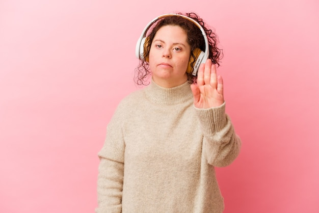 Woman with down syndrome with headphones isolated on pink background standing with outstretched hand showing stop sign, preventing you.