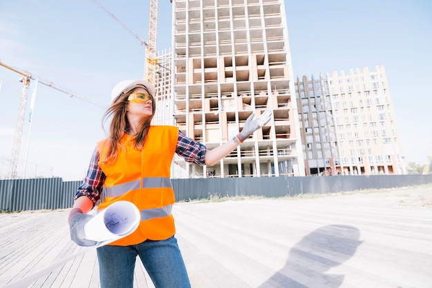 Woman with draftgesturing on construction site