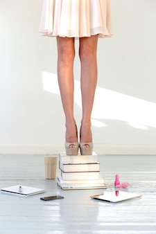 Woman with dress and shoes on stacked books