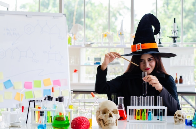 Woman with  dress witch and test tube in laboratory