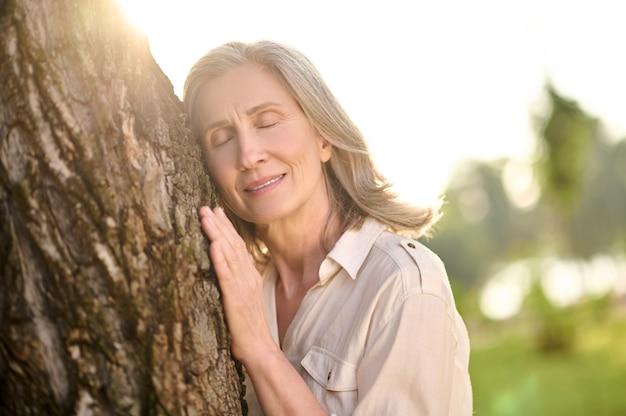 나무에 기대어 처진 눈꺼풀을 가진 여자