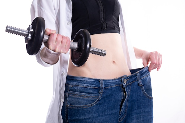 A woman with a dumbbell in her hand shows how much weight she lost. the concept of a healthy lifestyle and sports