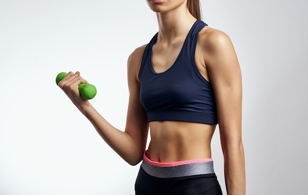 Woman with dumbbells in hand on light background cropped view of short t-shirt fitness. high quality photo