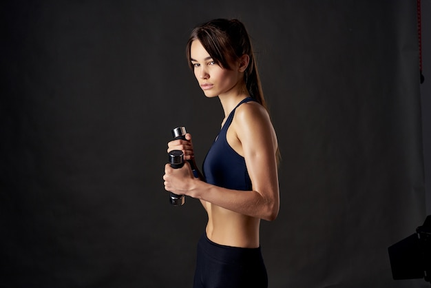 Woman with dumbbells in hands slim figure workout motivation