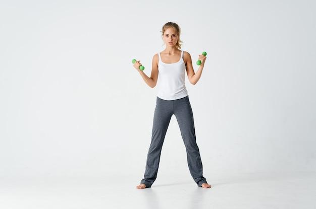 Женщина с гантелями в руках упражнения мотивации тренировки энергии